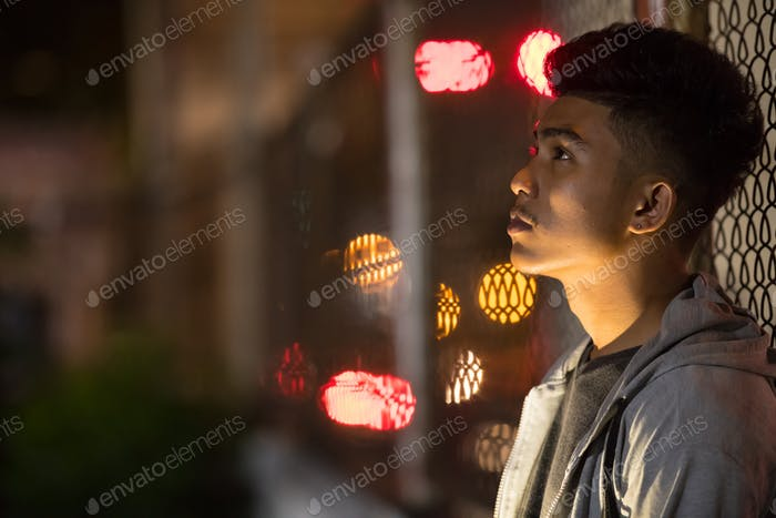 Face of sad young Asian man leaning on fence in the city streets