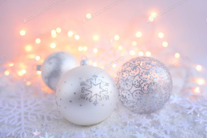Christmas decorative balls on snow and Christmas lights. Festive
