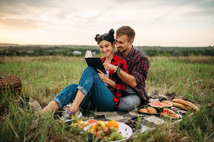 Couple reads book together, picnic in the field