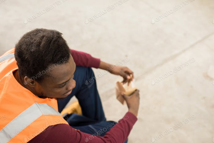 Calm worker in orange vest having lunch break