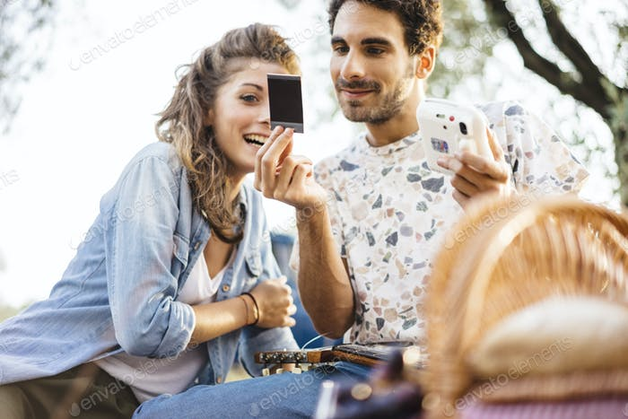Pareja romántica tomando un selfie con una cámara vintage en el país de la Toscana