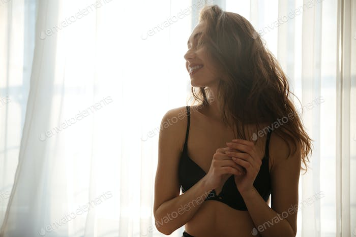 Woman wearing black lingerie standing in front of the window
