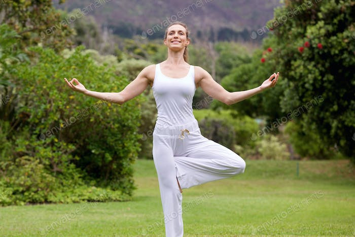 Smiling yoga woman standing on one leg in park