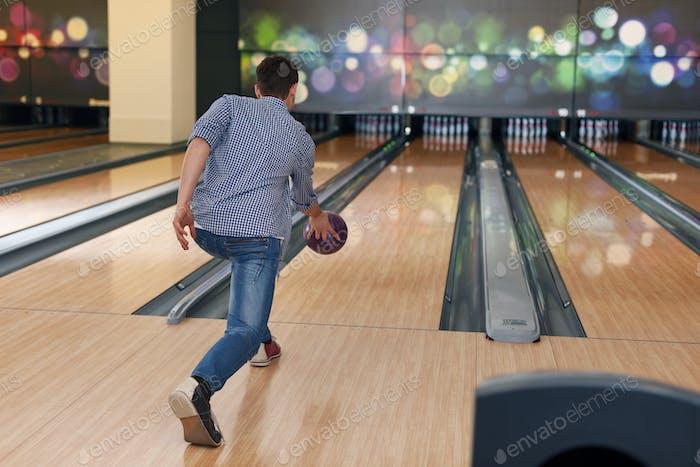 Mann während des Werfens Bowlingball