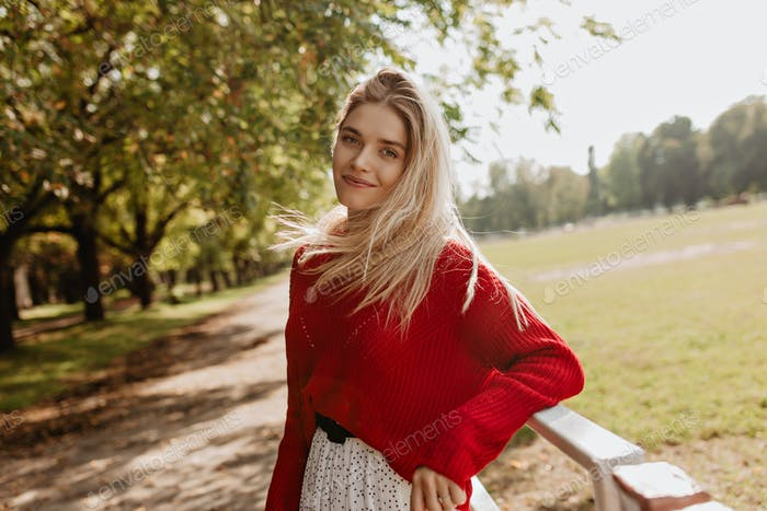 Cheerful girl with a natural make-up smiling gladly into the camera. Pretty blonde happily posing i