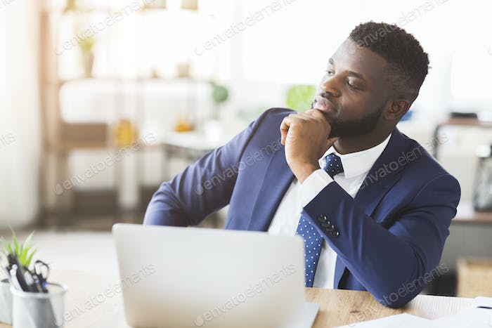 Pensive businessman working on new business plan in office