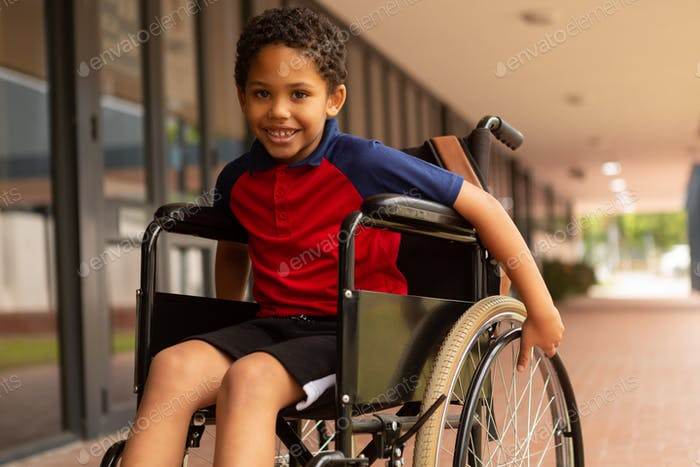 Smiling disabled schoolboy looking at camera in corridor at elementary school