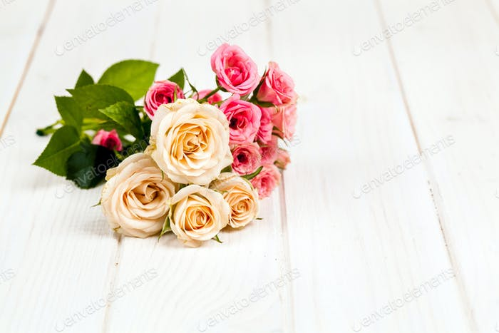 roses on white wooden planks background. flowers