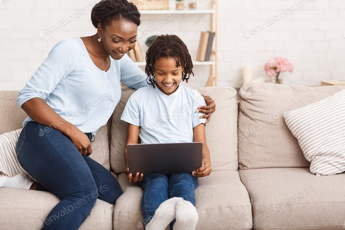 Afro mom and daughter using laptop on sofa