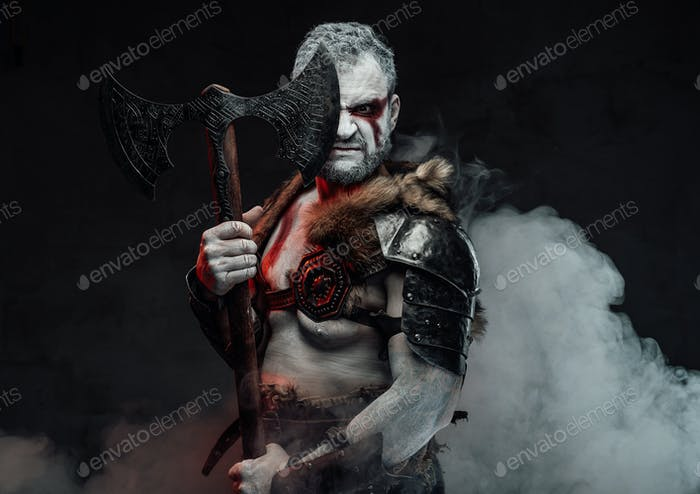 Aggressive mythical fighter in smoke with axe in studio