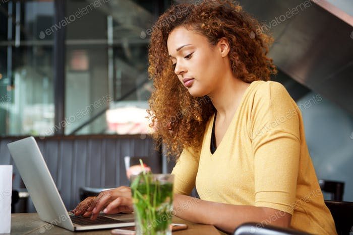 young woman sitting at cafe with laptop