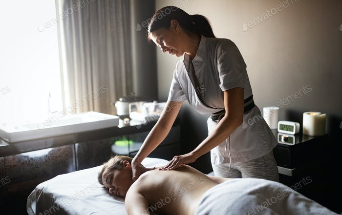 Masseur doing massage on woman body in the spa salon. Beauty treatment concept