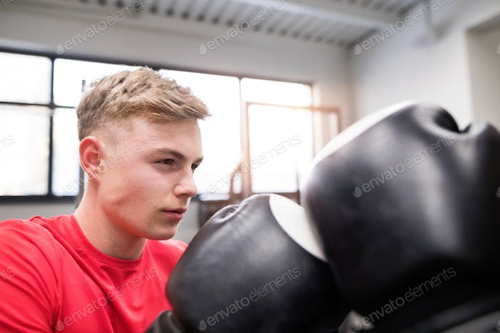 Fit handsome man in gym boxing with his unrecognizable rival.