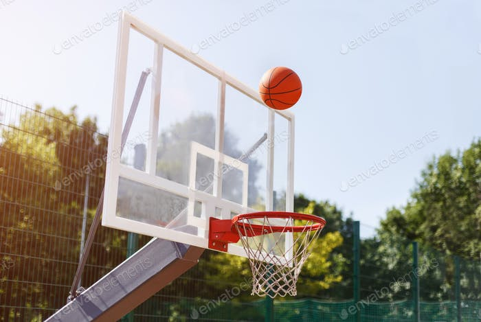 Basketball ball going through basket at outdoor sports arena, empty space