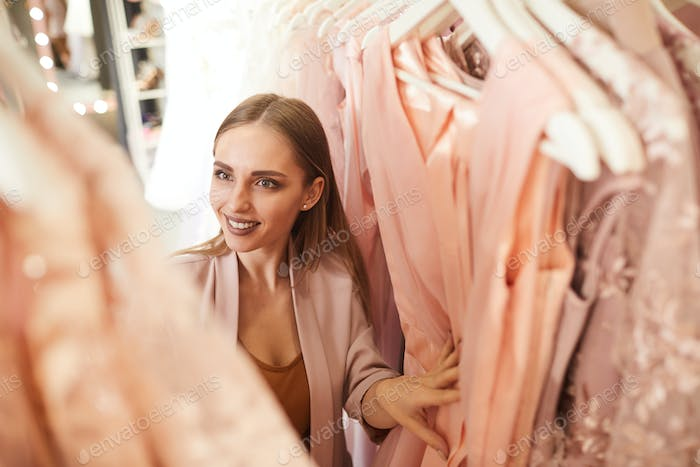 Excited Woman Choosing Dress in Boutique