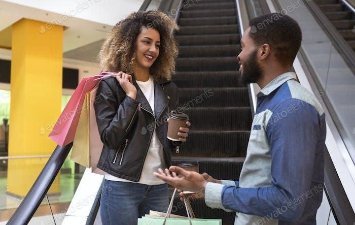 Веселая африканская пара приятно говорить с кофе идти