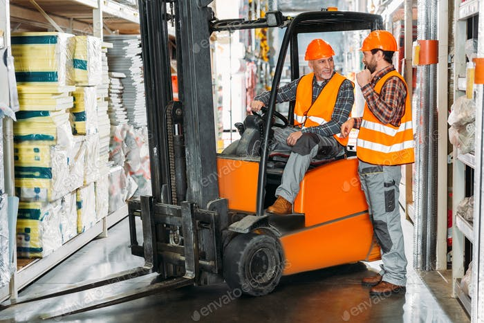 two male workers using forklift machine in storehouse