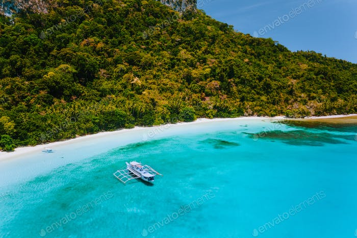 Aerial view of boat moored at secluded tropical beach with white sand, turquoise colored ocean