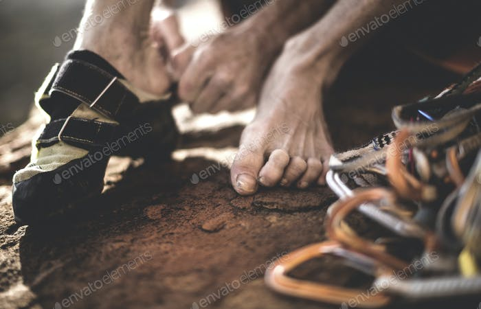 Close up of a free climber putting on rock climbing shoes with a pile of carabiners and rope.