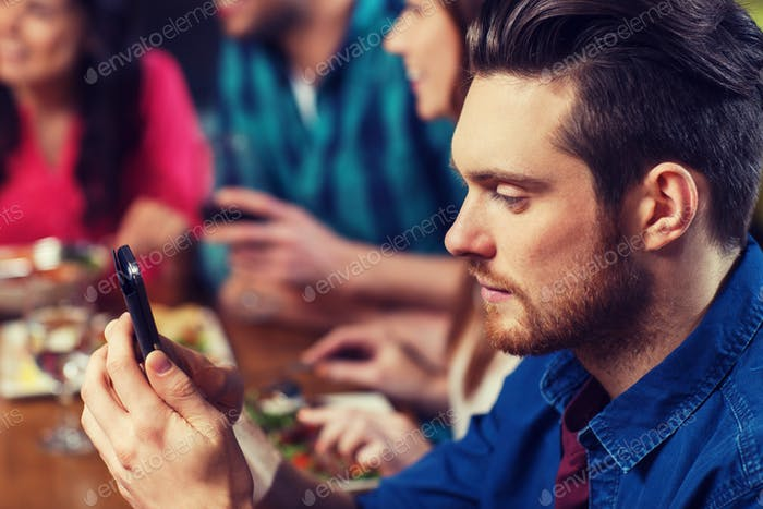 man with smartphone and friends at restaurant