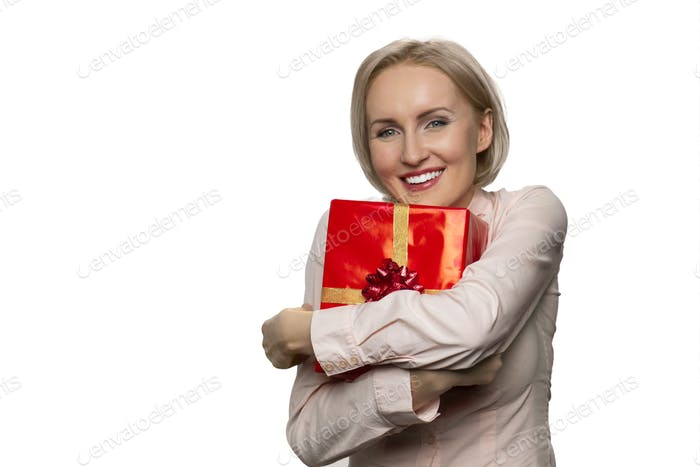 Portrait of smiling woman holding in hands hugging celebratory gift box