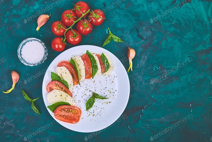 Italian caprese salad with sliced tomatoes, mozzarella cheese, basil, olive oil.