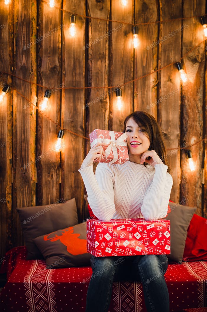 Smiling young woman with a gifts and Christmas tree
