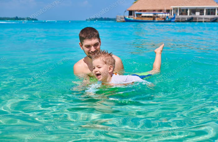 Toddler boy learns to swim with father