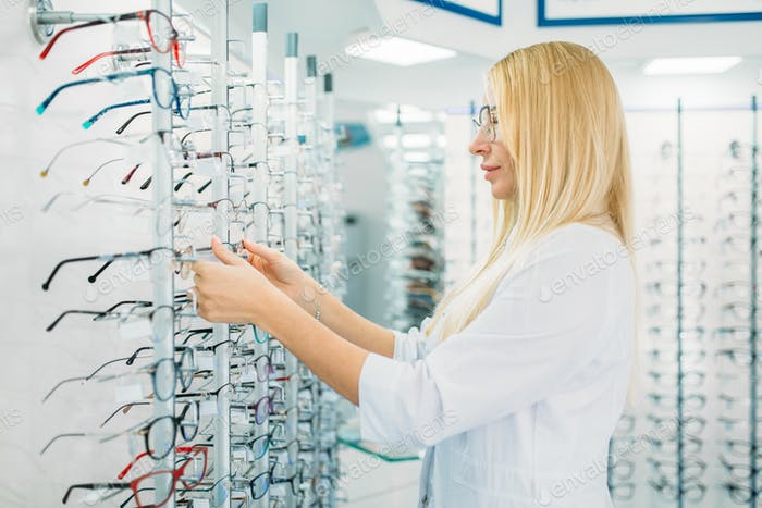 Female optometrist shows glasses in optics store