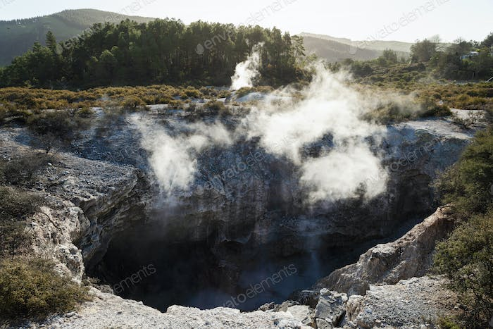View into a crater with geothermal heat steam rising from the water