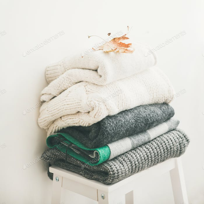 Pile of warm winter sweaters and blankets, square crop