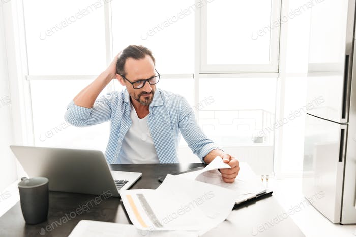 Confused mature man working with documents