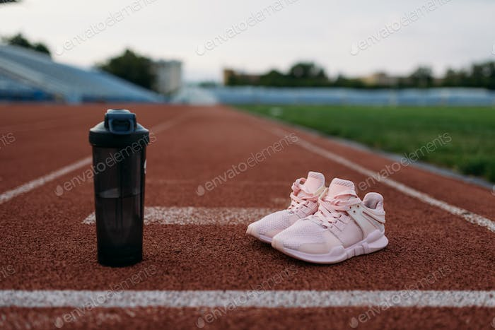 Sport shoes and bottle of water on stadium, nobody