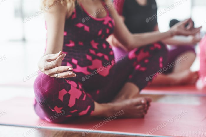 Focused photo of two pregnant woman sitting in yoga position doing exercises