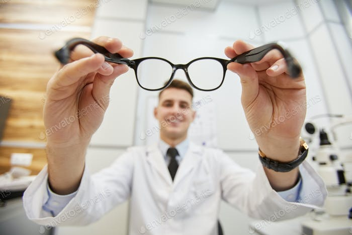 Young Optician Holding Glasses
