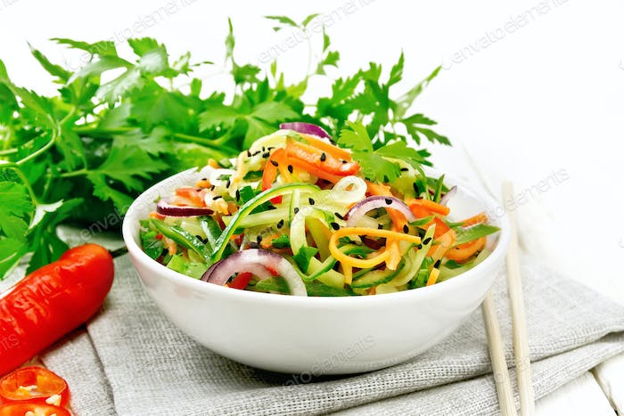 Salad of cucumber in bowl on board
