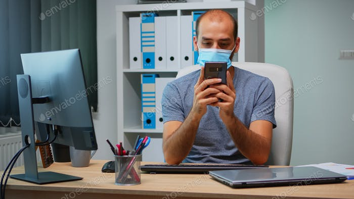 Office worker with mask using phone