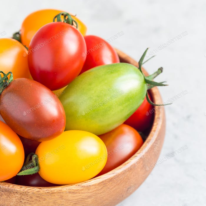 Small colorful cherry tomatoes in wooden bowl on a table, square