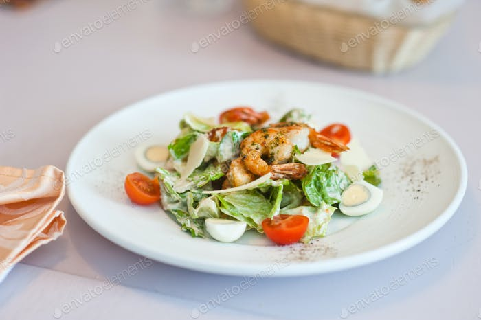 Shrimp salad in a white plate on a table at cafe. Shallow depth of field