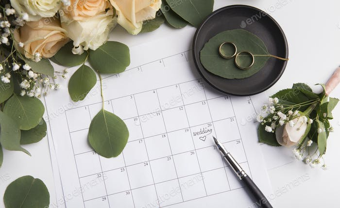 Waiting for wedding date which writing by pen in paper calendar