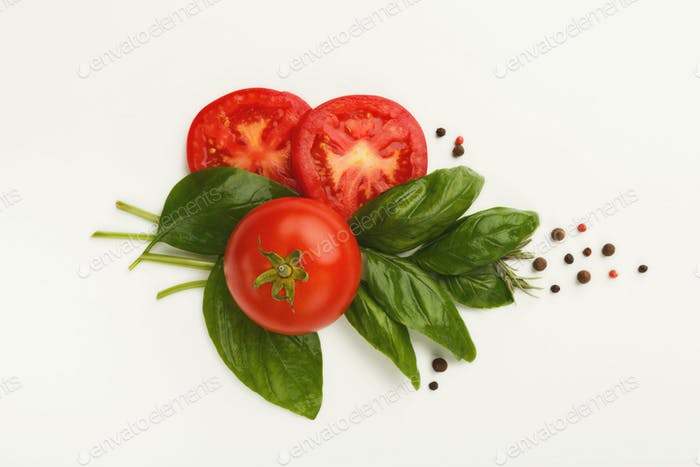 Red tomatoes and basil leaves isolated on white