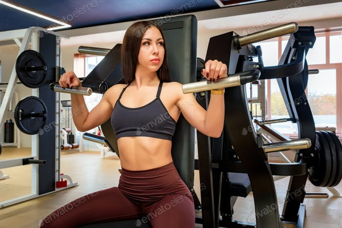 Young professional female athlete in sportswear sits in gym