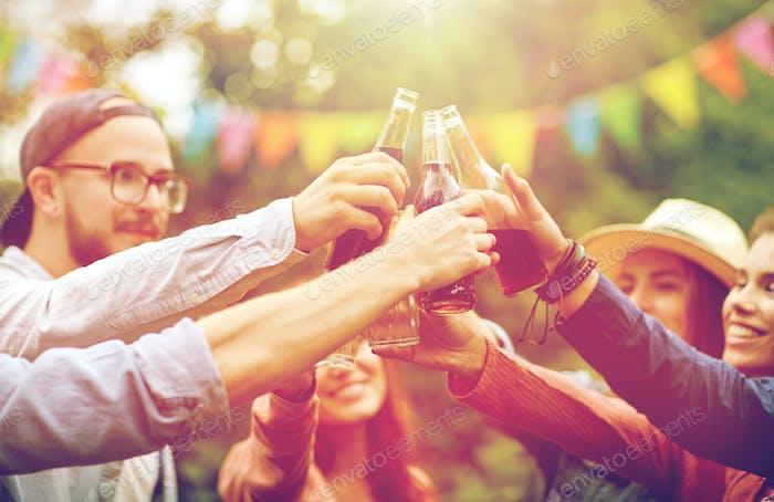 happy friends clinking glasses at summer garden