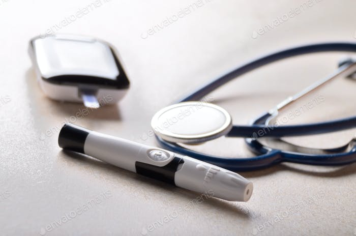Personal blood glucose meter and lancet with stethoscope on the