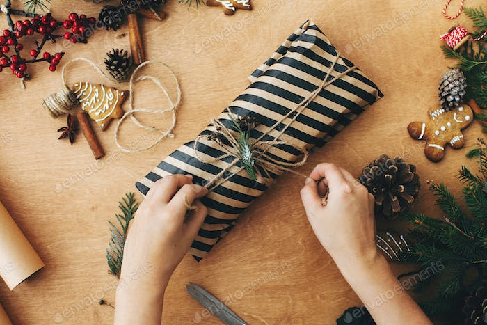Wrapping rustic christmas present. Hands wrapping christmas gift