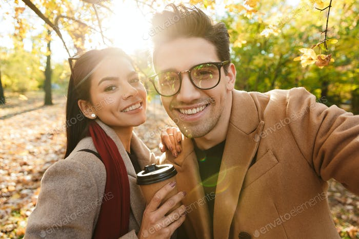 Portrait of happy couple drinking takeaway coffee and smiling at camera while walking in autumn park