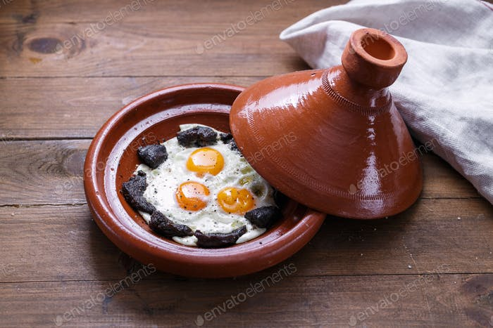Close view of fried egg and beef in tajine dish, traditional Moroccan dish