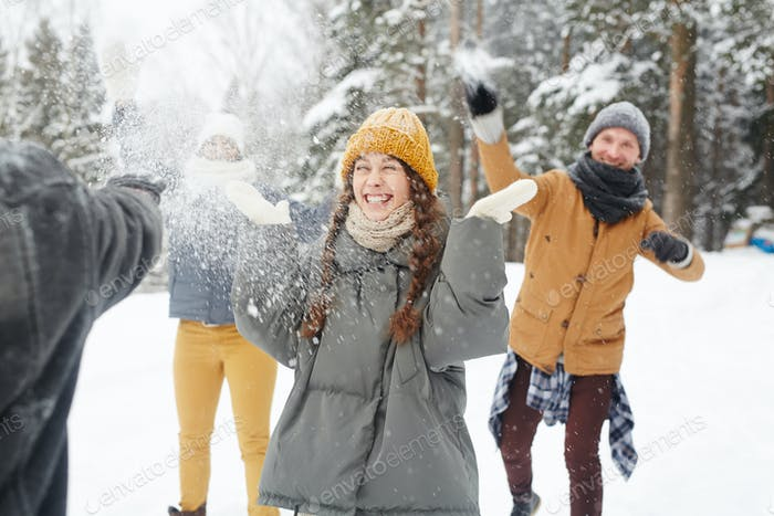 Happy friends having snowball fight