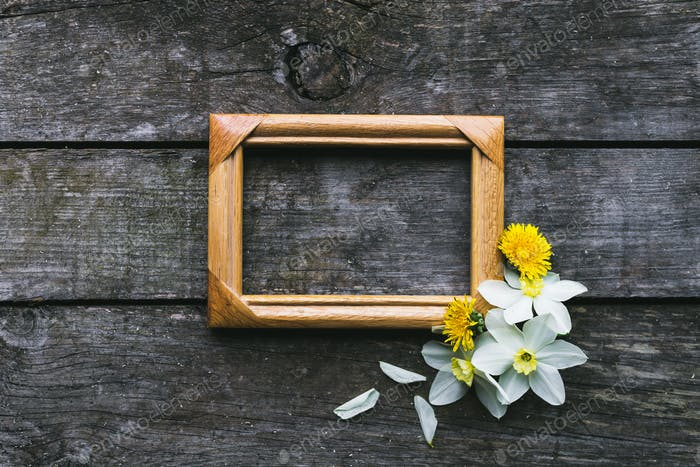 Spring flowers and frame on a old wooden background