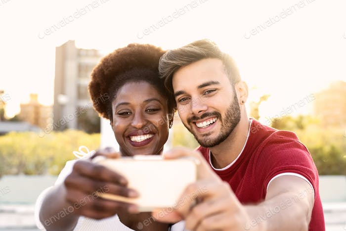 Happy couple taking selfie with mobile smartphone outdoor